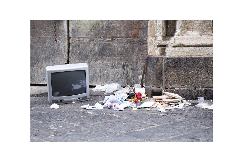 televisore abbandonato sul marciapiede con rifiuti